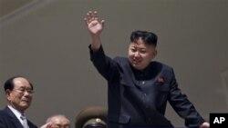 Pemimpin Korut, Kim Jong Un melambai kepada warga pada perayaan HUT ke-100 mendiang Kim Il Sung di Pyongyang, Minggu (15/4).