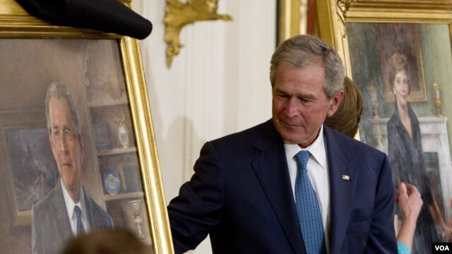 Former President George W. Bush and former first lady Laura Bush, right, unveil their portraits in the East Room of the White House in Washington, Thursday, May 31, 2012