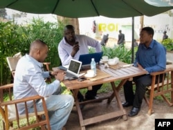 FILE - Men work on their laptops at the Endiro Cade in Kampala, Uganda.