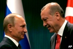 FILE - Turkish President Recep Tayyip Erdogan, right, shakes hands with Russian President Vladimir Putin in Ankara, Turkey, Sept. 28, 2017.