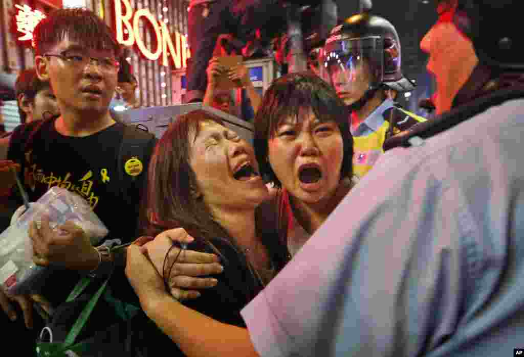 Protesters cry as the police officers try to stop them from blocking the road in the Mong Kok district of Hong Kong, Nov. 26, 2014.