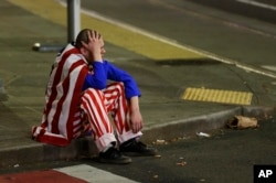A man dressed in red-white-and-blue sits on the curb during a protest against President-elect Donald Trump in Seattle's Capitol Hill neighborhood, Nov. 9, 2016.