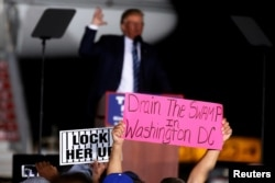 "A man holds up a ""Drain the Swamp in Washington DC"" sign as then-Republican presidential nominee Donald Trump attends a campaign event on the tarmac of the airport in Kinston, North Carolina, Oct. 26 2016."