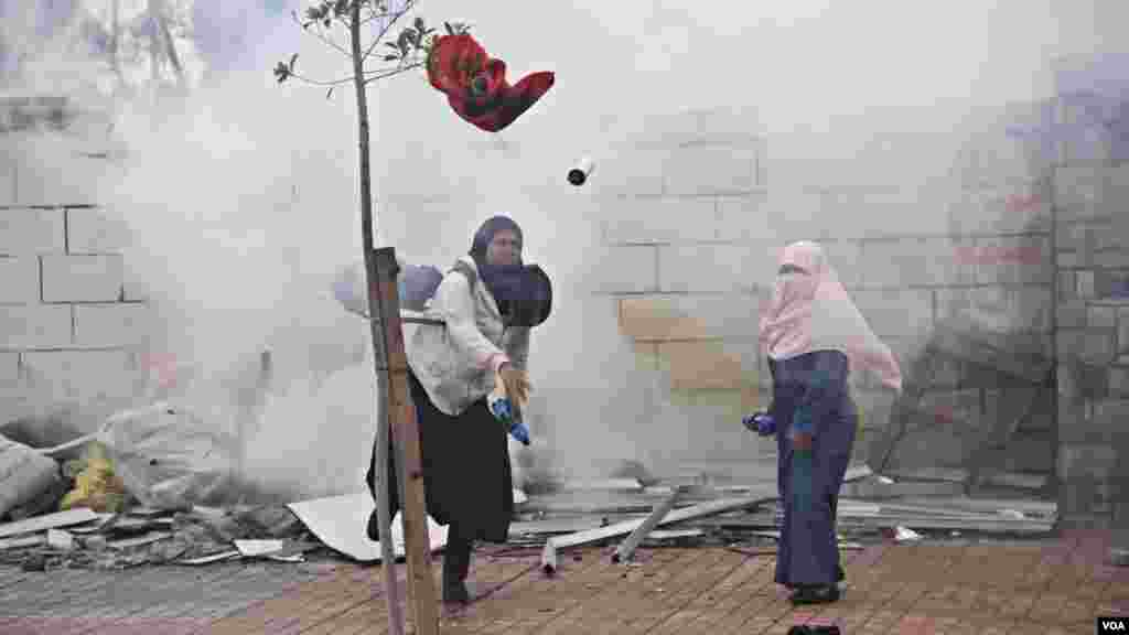 Female Islamist students throw projectiles at police during a protest at Al-Azhar University in Cairo, Dec. 11, 2013. (Hamada Elrasam for VOA)