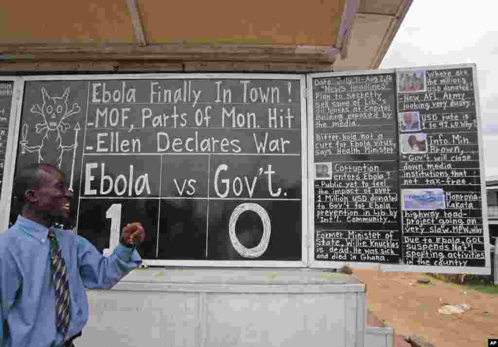 Social commentator Alfred Sirleaf gives comment on current events in Liberia including the deadly Ebola virus by writing them on a blackboard, in Monrovia, Liberia, July 31, 2014.