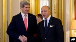 El secretario de Estado, John Kerry, saluda a su homólogo francés, Laurent Fabius, en París. Kerry vuela de regreso a Washington.