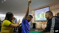Carlos Junior celebrates at the end of the match between Brazil and Mexico with the help of an interpreter who used tactile signing and a model soccer field to recount the passes, goals and fouls of Brazil's 2-0 victory.
