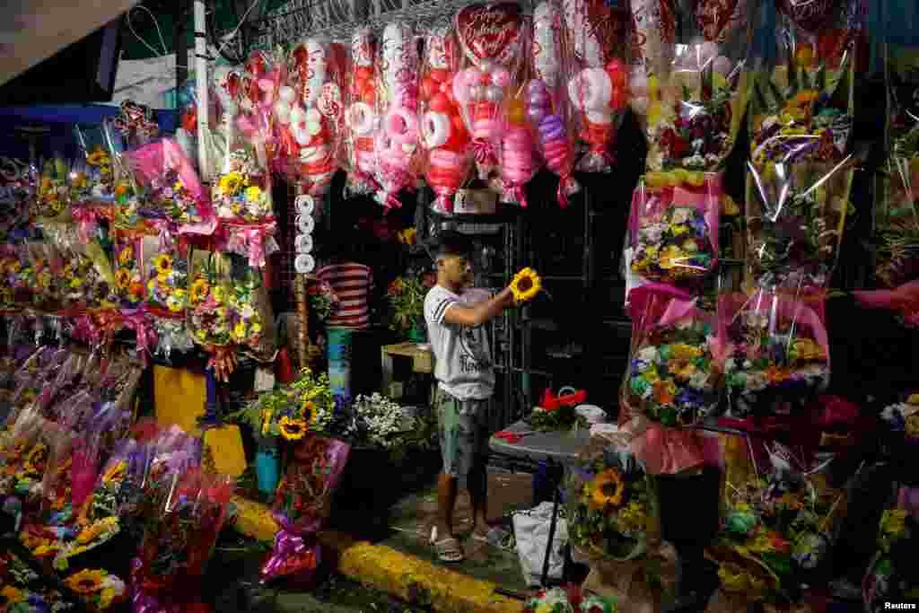آماده شدن یک مغازهدار با چیدن دستههای گل برای فروش روز ولنتاین یا روز عشاق در مانیل، فیلیپین
