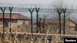 FILE - North Korean soldiers patrol behind a border fence near the North Korean town of Sinuiju, March 31, 2017.