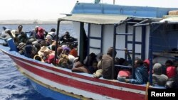 FILE - Illegal migrants who attempted to sail to Europe, sit in a boat carrying them back to Libya, after their boat was intercepted at sea by the Libyan coast guard, at Khoms, Libya, May 6, 2015.