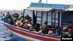 Illegal migrants who attempted to sail to Europe, sit in a boat carrying them back to Libya, after their boat was intercepted at sea by the Libyan coast guard, at Khoms, Libya, May 6, 2015.