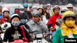 FILE - A motorist talks on his mobile phone while waiting at a traffic junction in Hanoi in this 2011 photo.