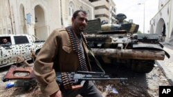 A rebel fighter walks beside a captured Gaddafi forces tank in Tripoli street April 22, 2011. Rebel fighters pushed Gaddafi forces off the upper part of Tripoli Street in central Misrata during an overnight offense.