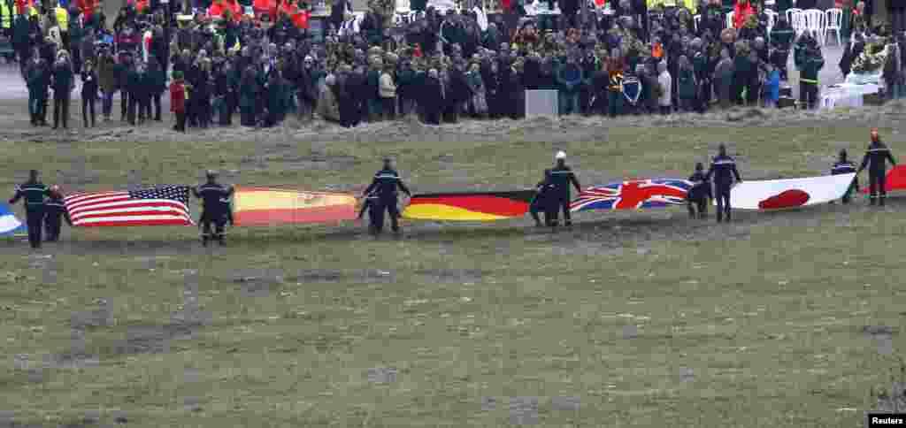 Quốc kỳ đại diện cho quốc tịch của một số nạn nhân khi gia đình và người thân tụ tập gần khu vực tai nạn của chiếc máy bay trong dãy núi Alps của Pháp.