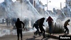 Para demonstran Palestina berlarian menghindari gas air mata yang ditembakkan pasukan keamanan Israel dalam aksi protes di dekat Ramallah, Tepi Barat, Kamis (7/12).