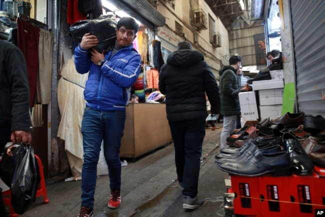 FILE - People conduct their business at the Grand Bazaar in Tehran, Iran, Feb. 7, 2019.