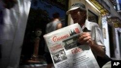 FILE - A vendor holds a copy of Cuba's state newspaper Granma, in Havana, Cuba, Aug. 13, 2015.
