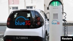 A BlueSG electric car-sharing vehicle is parked at a charging station in a public housing estate in Singapore