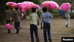 Vendors hold bags of cotton candy for sale as they look for customers in New Delhi on June 28, 2012. India's food inflation rose to 10.66 percent in May from 10.18 percent in April, latest figures show.