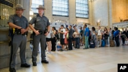 New York state police officers stand guard as travelers line up to buy train tickets at Grand Central Terminal in New York, July 1, 2016.