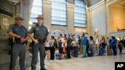Cảnh sát đứng bảo vệ trong khi người dân xếp hàng mua vé tàu tại Nhà ga Trung tâm ở New York, ngày 1 tháng 7 năm 2016.