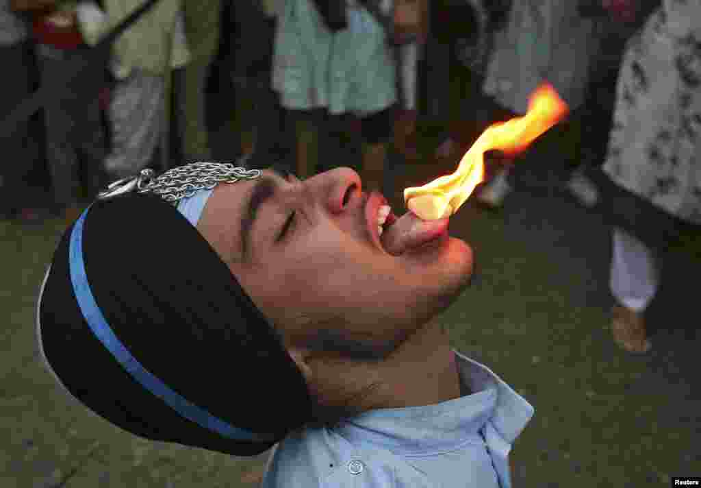 A Sikh man performs a stunt with fire during the celebrations of the 410th anniversary of the installation of the Guru Granth Sahib, the religious book of Sikhs, in the northern Indian city of Amritsar.