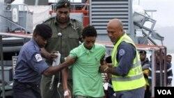 Uno de los jóvenes neocelandeses rescatados desciende del barco atunero que los encontró a la deriva.