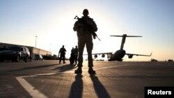 Un soldado monta guardia frente a un avión C-17 Globemaster III. Un 47% del público estadounidense no quiere que se reduzca el gasto militar.