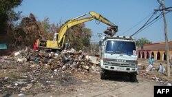 Xe xúc đất được sử dụng để dọn những đống rác do lũ lụt để lại trong quận Muang Ake, bên ngoài thủ đô Bangkok củaThái Lan