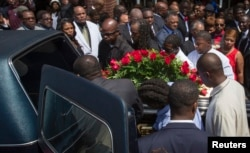 Lesley McSpadden (R, in red) watches as the casket containing the body of her son Michael Brown lifted into a hearse after his funeral services at Friendly Temple Missionary Baptist Church, St. Louis, Missouri, August 25, 2014.