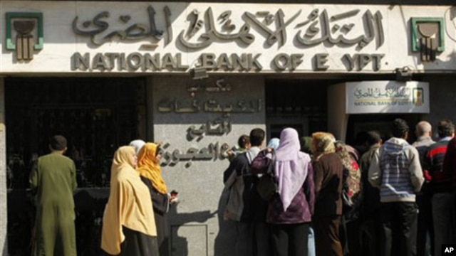 People in Cairo wait to withdraw money from the bank.  Egypt's currency has dropped in value to its lowest level in 6 years, February 3, 2011