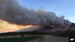 A wildfire burns off of the hills next to CA-126 highway, just northwest of Fillmore, California, Dec. 7, 2017.