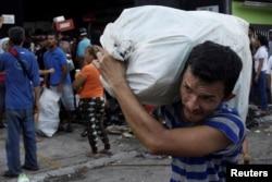 People carry goods taken from a food store in La Fria, Venezuela, Dec. 17, 2016.