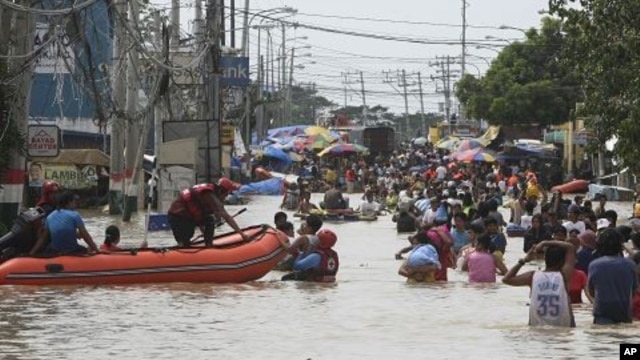 Residents wade through floodwaters as flooding continues for the fourth day at Calumpit township, Bulacan province north of Manila, Philippines, October 2, 2011.