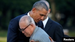 U.S. President Barack Obama (L) hugs atomic bomb survivor Shigeaki Mori as he visits Hiroshima Peace Memorial Park in Hiroshima, Japan, May 27, 2016.