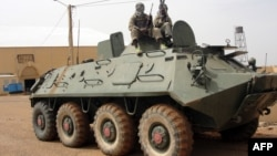 Fighters of the Islamic group, the Movement for Unity and Jihad in West Africa [MUJAO] - an Al-Qaida offshoot - stand guard on a tank abandoned by the Malian Army, near Gao airport, Mali, August 7, 2012.
