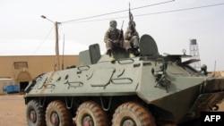 Des combattants du Mujao, groupe lié à Al-Qaïda au Maghreb Islamique (Aqmi), montent la garde sur un char abandonné par l'armée malienne, près de l'aéroport de Gao, au Mali, 7 août, 2012.