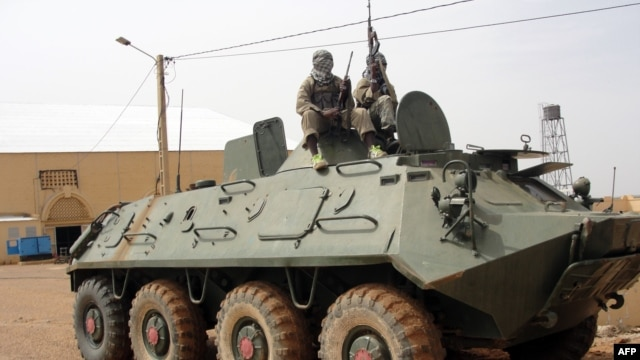 Fighters of the Islamic group, the al-Qaeda offshoot MUJAO stand guard on a tank abandoned by the Malian Army, near Gao airport, August 7, 2012.