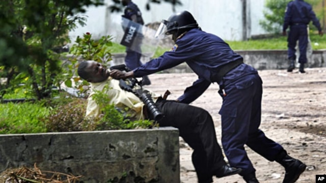 A supporter of Congolese opposition leader Etienne Tshisekedi is grabbed by a Congolese riot police officer outside his candidate's headquarters in Kinshasa, Democratic Republic of Congo, December 8, 2011