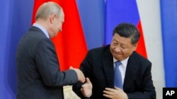 Chinese President Xi Jinping and Russian President Vladimir Putin shake hands during a ceremony at which Xi was presented with an honorary degree from St. Petersburg State University in St. Petersburg, Russia, June 6, 2019.