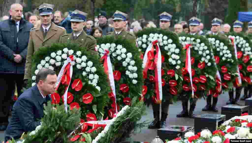 លោកប្រធានាធិបតី Andrzej Duda (រូបឆ្វេង) ដាក់កម្រងផ្កានៅកន្លែងបញ្ចុះសពរបស់ជនរងគ្រោះនៃការធ្លាក់យន្តហោះរបស់ប្រធានាធិបតី ក្នុងពិធីបុណ្យដើម្បីរំលឹកខួបទី៦នៃការធ្លាក់យន្តហោះនោះ នៅកន្លែងបញ្ចុះសពយោធា Powazki នៅក្នុងក្រុងវ៉ាសូរី ប្រទេសប៉ូឡូញ។ លោកប្រធានាធិបតី Lech Kaczynski ភរិយារបស់លោកឈ្មោះ Maria Kaczynska និងមនុស្ស៩៤នាក់ផ្សេងទៀតបានស្លាប់ កាលពីថ្ងៃទី១០ ខែមេសា ឆ្នាំ២០១០ នៅពេលដែលយន្តហោះរបស់ប្រធានាធិបតីប៉ូឡូញបានធ្លាក់នៅក្នុងក្រុង Smolensk ប្រទេសរុស្ស៊ី។