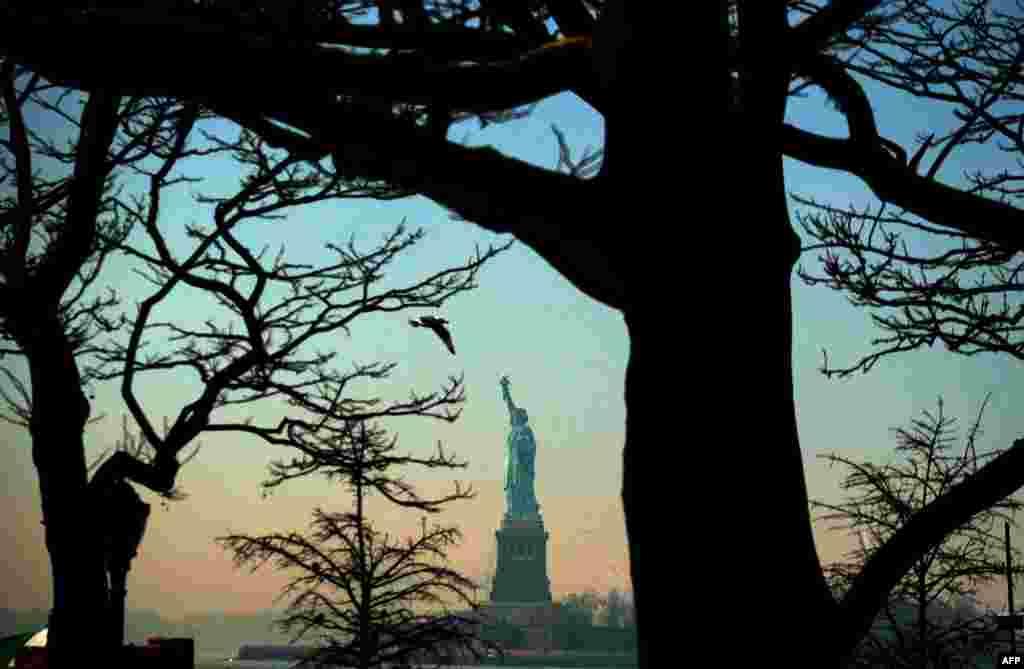 Patung Liberty terlihat dari taman Battery pada sore hari di New York.