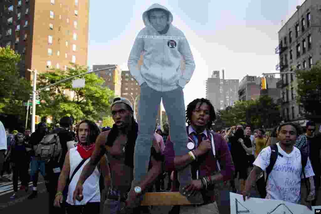 Waandamanaji wakitembea katika mtaa wa Lower East Side mjini New York huku wakiwa wameshikilia sanamu la Trayvon Martin wakati wa maandamano baada ya kuachiwa kwa George Zimmerman, July 14, 2013.