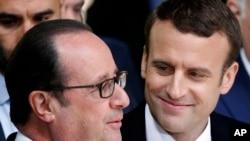 Le président français sortant François Hollande, à gauche, discute avec le président élu Emmanuel Macron lors de la cérémonie de la commémoration de l'abolition de l'esclavage, à Paris, France, 10 mai 2017.
