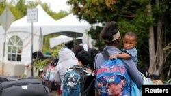 Yon gwoup moun ki idantifye tèt yo kòm ayisyen ki soti Etazini e kap mande azil sou fwontyè Kanada. 7 out 2017. (Foto: REUTERS/Christinne Muschi)