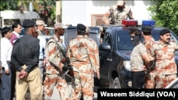 6일 파키스탄 카라치 주재 아프가니스탄 영사관 총격 현장에서 군경이 수습작업을 진행하고 있다.