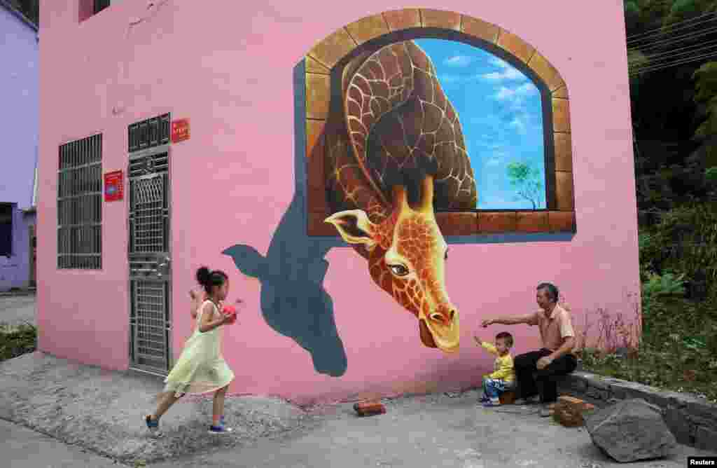 Tourists play in front of a 3D painting on the wall of a house in Luoyuan village, Jinhua, Zhejiang province, Aug. 26, 2015.