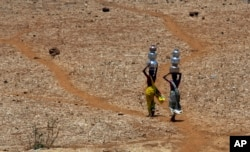 FILE - Indian women walk home after collecting drinking water from a well at Mengal Pada in Thane district in Maharashtra state, May 4, 2016.
