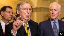 FILE - Senate Majority Leader Mitch McConnell of Ky., accompanied by Sen. John Barrasso, R-Wyo., left, and Senate Majority Whip John Cornyn of Texas., meet with reporters on Capitol Hill.