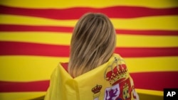 Жінка з іспанським прапором дивиться на величезний прапор Каталонії